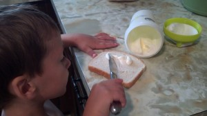 Spreading his butter on some bread!
